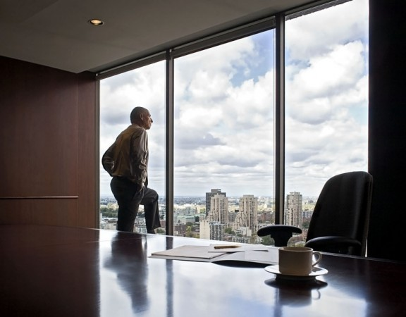 Senior businessman looking out an office window.  Model Released.